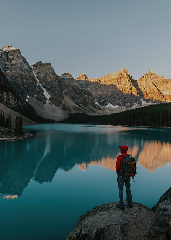 A person stands on a run in front of Moraine Lake at sunrise
