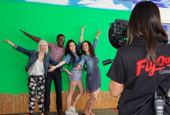 "Four people pose with ""airplane arms"" for a photo in front of a green screen"