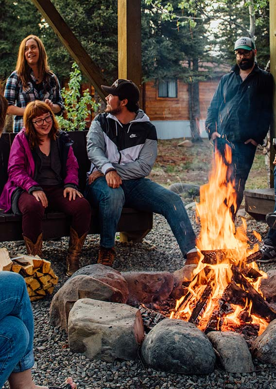 A group of people sit around a bonfire laughing and smiling