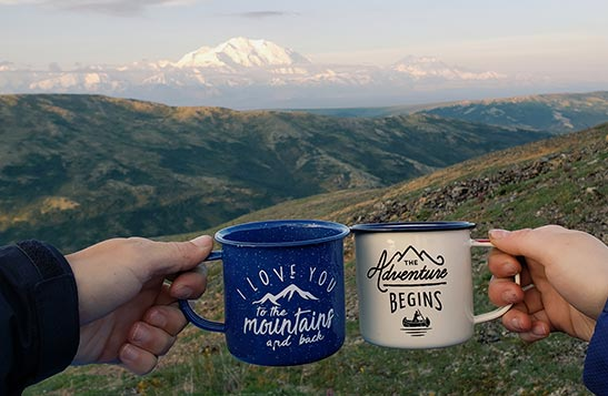 Two enamel coffee cups in a cheers in front of a wide tundra vista.