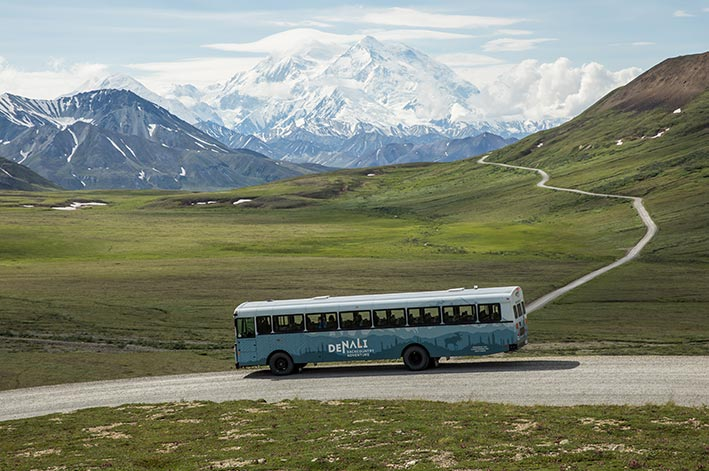 A bus parked at an overlook with a view towards Denali.