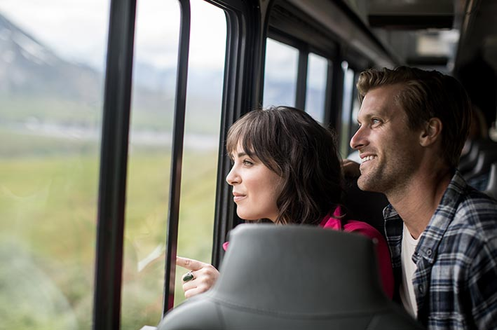 Two people look out a bus window.