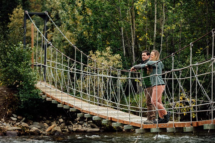 Two hikers stand on a small suspension foot bridge.