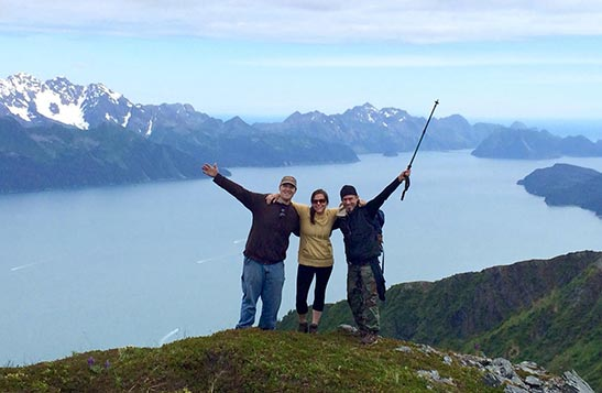 Three people stand at a mountain above the sea.