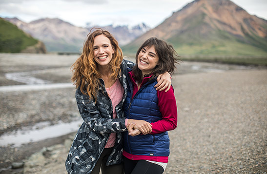 Two women hugging and smiling with mountains and river in the background