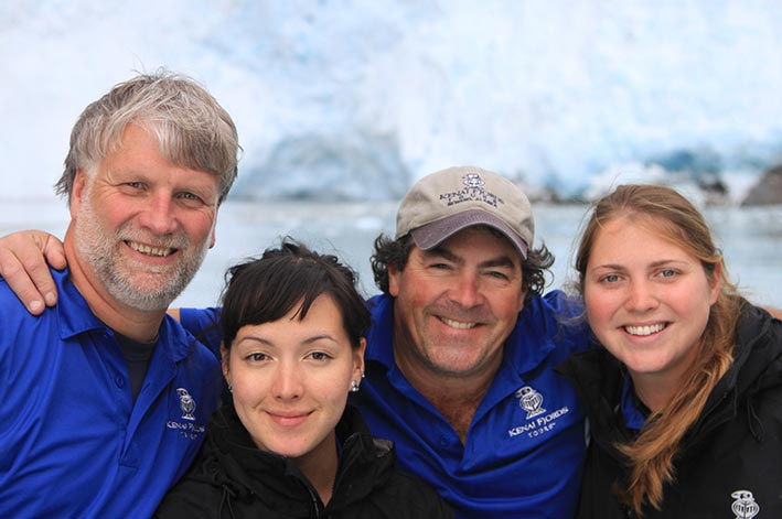 Four Kenai Fjords Tours workers smile in front of a glacier
