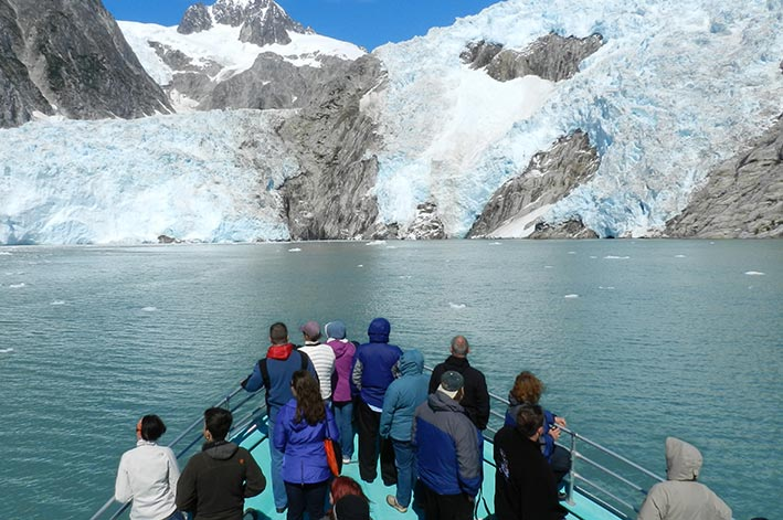 Boat guests stand at the prow of a boat before a tidewater glacier.
