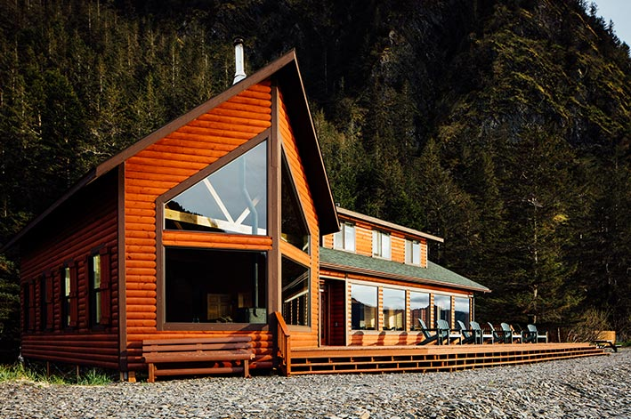 A rustic wooden lodge between a rocky beach and forested mountainside