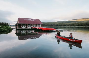 Two canoers paddle away from a rustic boathouse on a calm lake