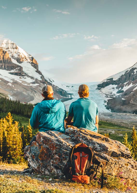 Two hikers take a break on a rock next to a forest, looking towards the Athabasca Glacier