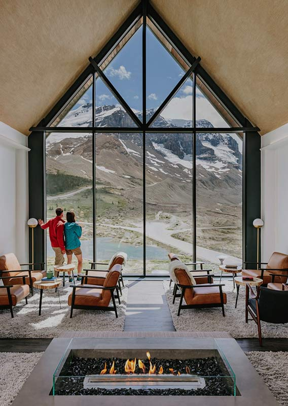 A lounge with a large window view towards mountains and a glacier.