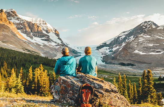 Two people sit on a rock looking towards mountains and glaciers.