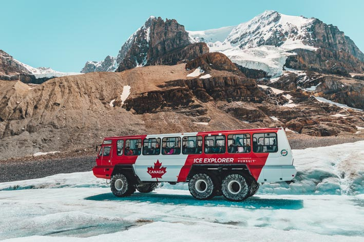 A red and white Ice Explorer vehicle moved on an ice road below a rocky mountainside