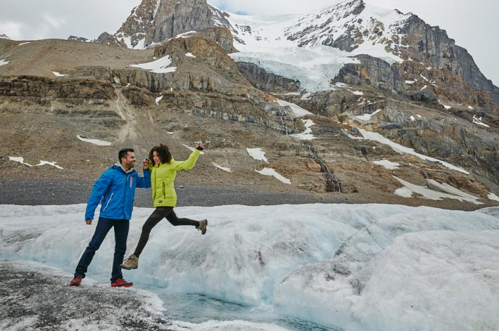 Two people jump from one part of a glacier to another