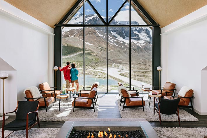 A lounge with a fireplace next to a large pointed window to a view of mountains and a glacier