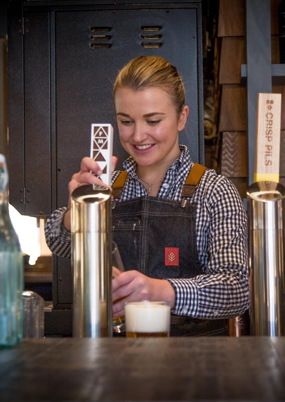 A bartender pours a pint of beer from a draught tap.