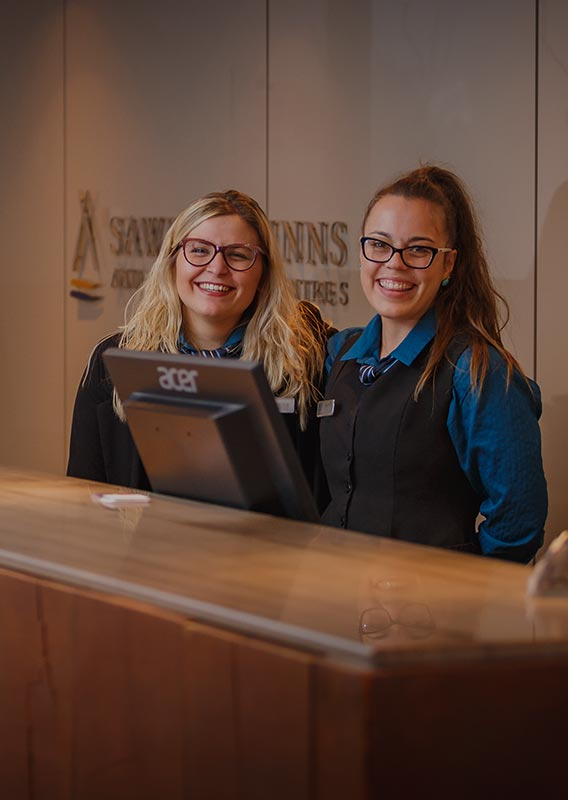 Two workers at a hotel front desk