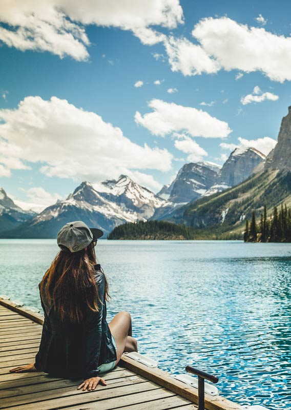 A person sits on a dock edge looking out across a blue lake towards mountains