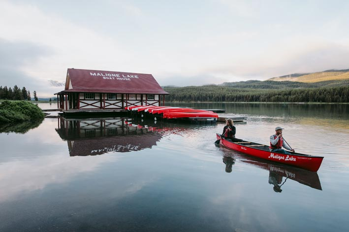 Two canoers paddle away from the Maligne Lake Boat House