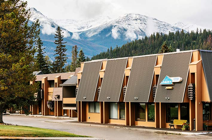 A hotel building in front of forested hillsides and mountains.