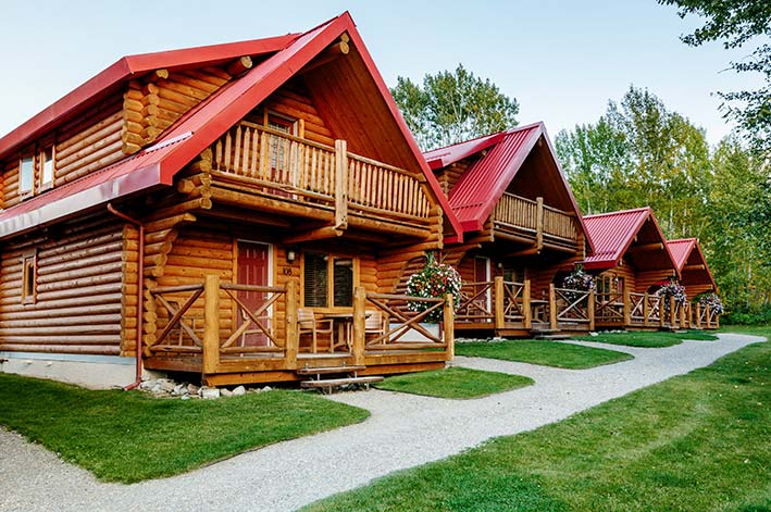 A row of wooden cabins with red roofs