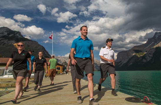 A group of boat and deck crew walk on a deck along a turquoise lake.
