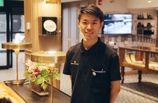 A hotel worker stands in an elegantly decorated lounge.
