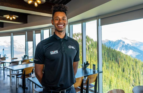 A worker smiles in a dining room that overlooks a forested mountainside.