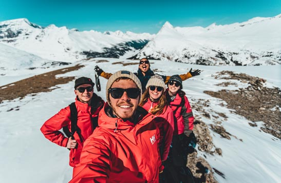 Five hikers smile for a wide-angle selfie in a rocky and snowy alpine environment.