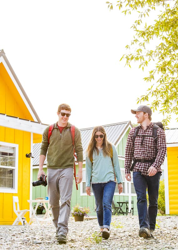 Three people ready for a hike walk between colorful tiny homes