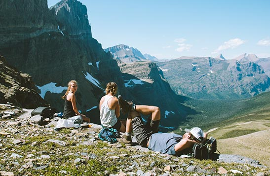 Three people sit in a rocky alpine meadow above a wide valley.