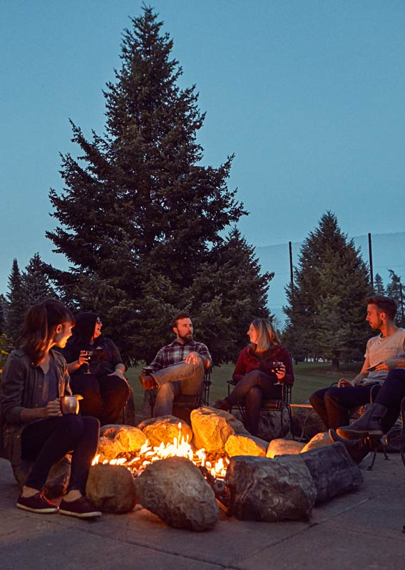A group of six people sit around a firepit on a dusky evening.