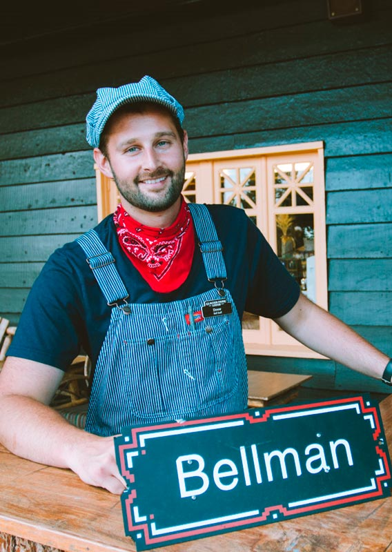 A bellman dressed in vintage-style overalls and hat smiles at the outdoor bellman desk.