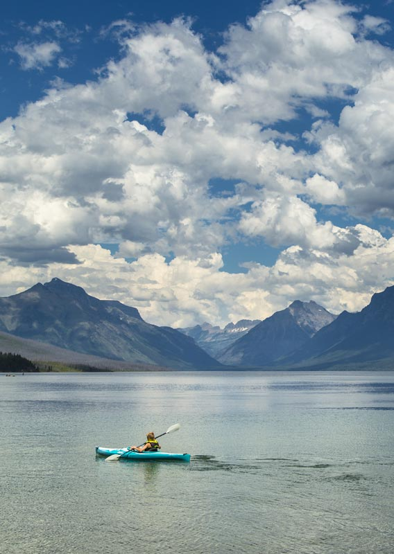 A kayaker paddles on a large lake surrounded by tree-covered mountains