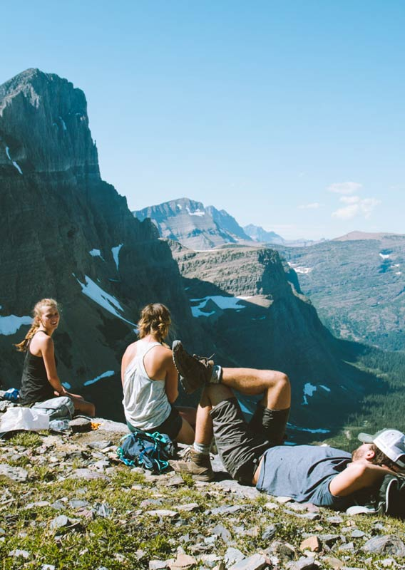 Hikers take a break and sit high above a wide forested valley.