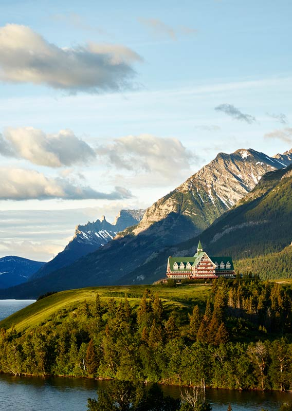 The Prince of Wales Hotel sits on a hill above a lake surrounded by mountains.