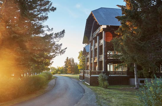 Early morning sun shines on the large wooden Glacier Park Lodge