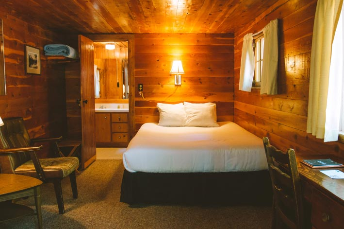 The inside of a rustic wooden cabin, with a warm glowing lamp above a bed