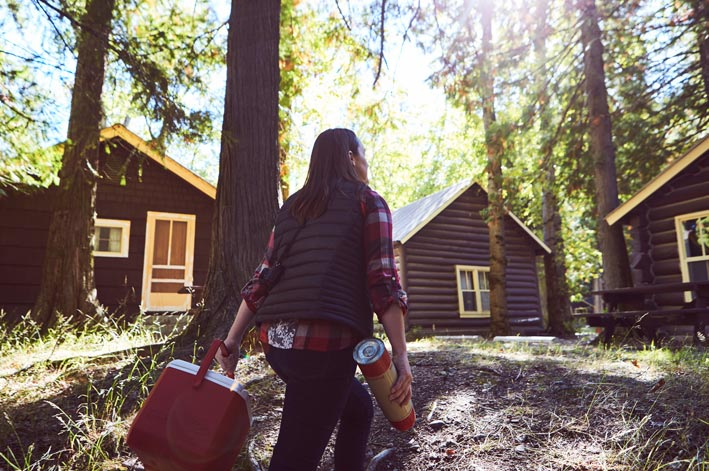 A woman walks under tall conifers between wooden cabins.
