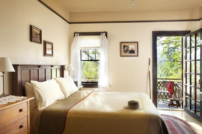 A hotel room overlooking green trees