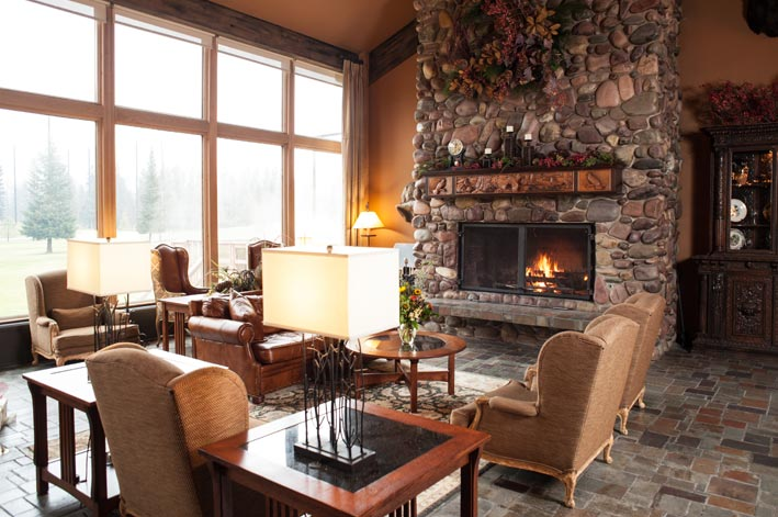The Grouse Mountain Lodge hotel lounge with stone fireplace and chairs around.
