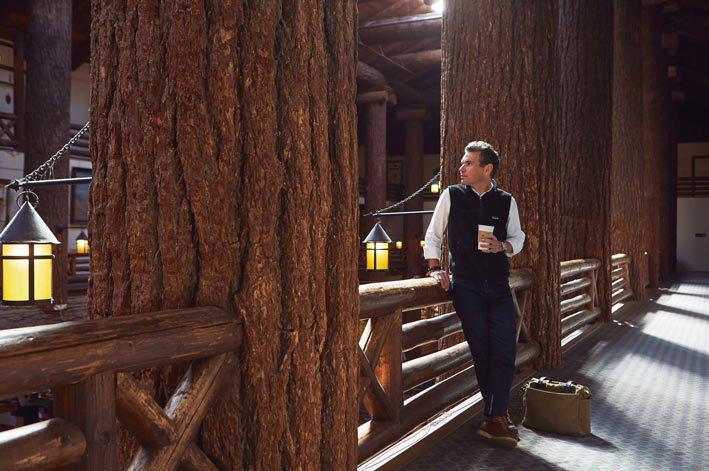 A man stands between large douglas fir tree trunk beams.