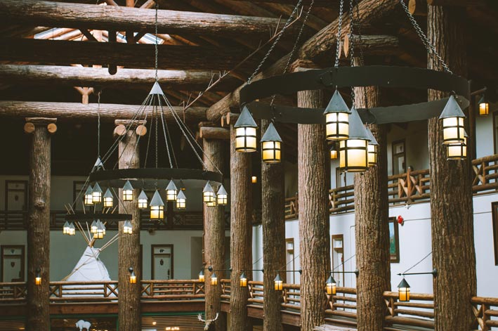 Rustic chandeliers hang from the ceiling of the wooden Glacier Park Lodge