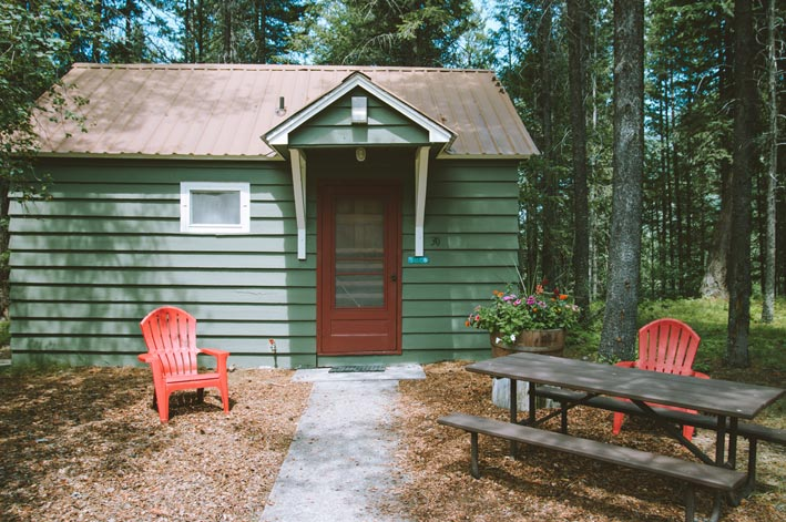 A green wooden cabin surrounded by trees with red chairs out front