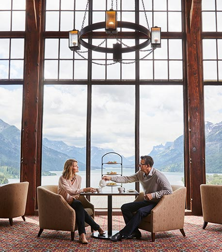 Two people sitting at a dining table in a restaurant with tall windows and a view of mountains.