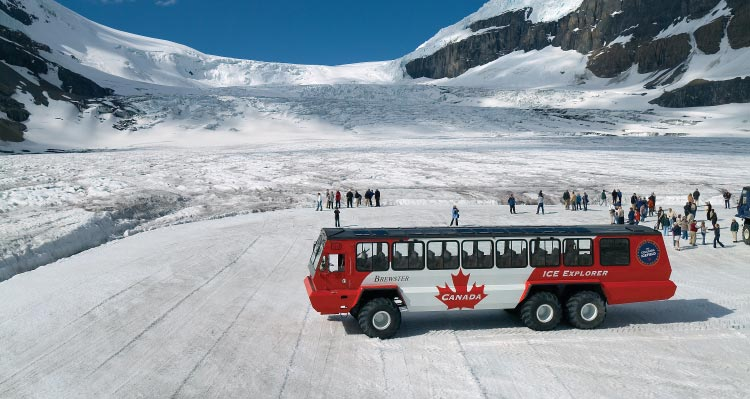 A Glacier Adventure Ice Explorer on the Columbia Icefield with groups of people stand on the icefield.