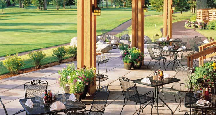 A patio adjacent to a lush golf course.