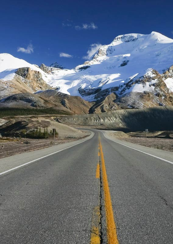 A road stretches towards ice-covered mountains.